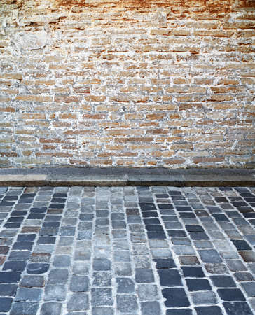 cobblestone street: brick wall with cobblestone street Stock Photo