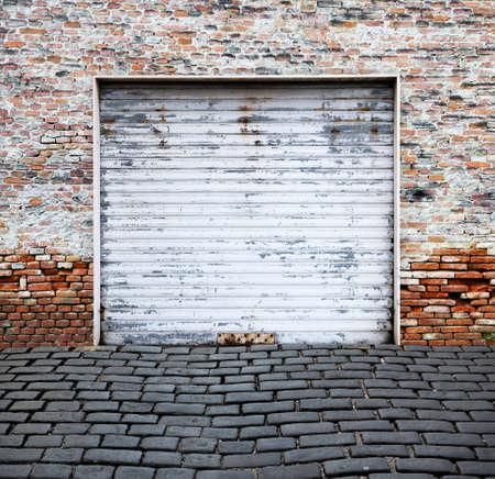 old roll up garage door on brick wall photo