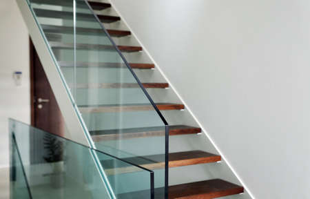 hardened: detail of hardened glass balustrade in house with wooden stairs Stock Photo