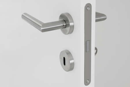 modern door handle on white open door Imagens - 28416737