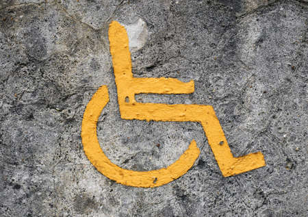 handicap handmade old sign on concrete wall Stock Photo