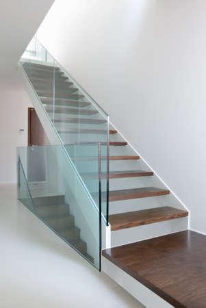 escaleras de madera con barandilla de cristal en suelo de epoxy interior y blanco moderno