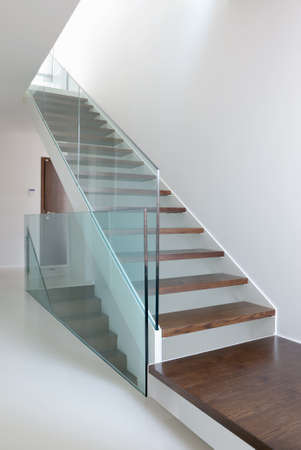 hardened: wooden stairs with glass balustrade in modern interior and white epoxy flooring Stock Photo
