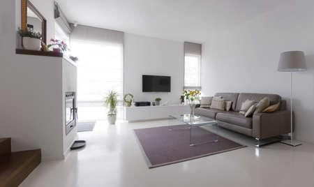 Wit woonkamer met taupe lederen sofa en glazen tafel