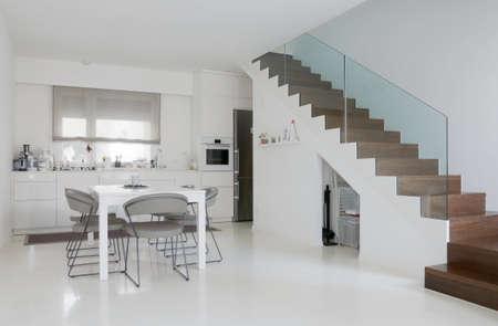 흰색 에폭시 바닥과 나무 계단 흰색 부엌과 식당