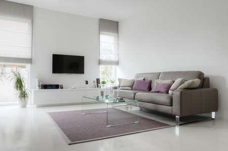 Wit woonkamer met taupe leren bank en glazen tafel op tapijt Stockfoto