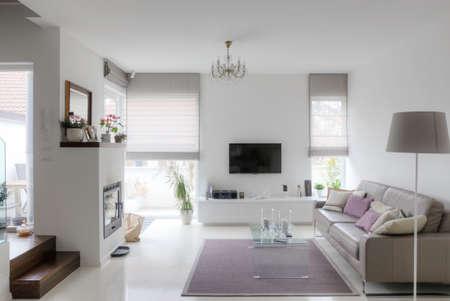 moderne woonkamer met taupe bank glazen tafel en open haard