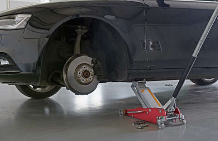 car in garage: detail of car on car jack with tire removed