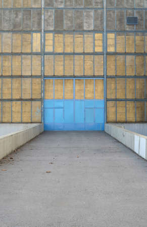 old industrial building with blue metal door photo