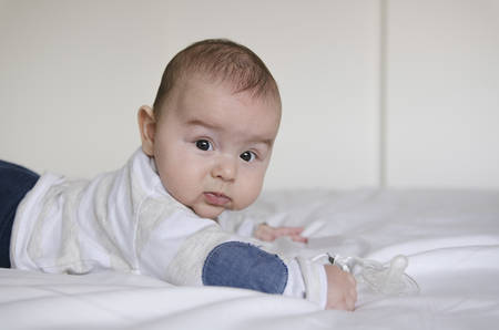 drool: baby boy lying on belly side view Stock Photo