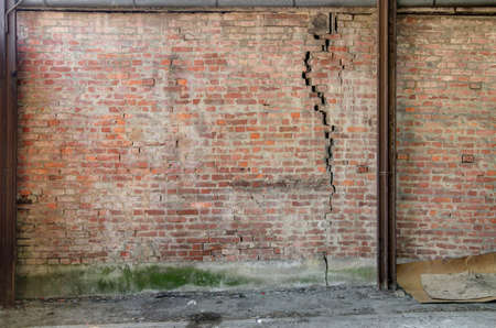 old weathered cracked facade brick wall background Stock Photo