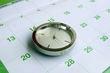 anticiparse: reloj de cromo aislado en calendario Foto de archivo