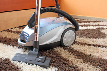 vacuuming: isolated vacuum cleaner on carpet Stock Photo
