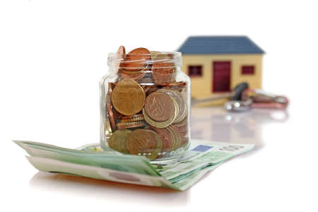 jar with coins in front of blurred house photo