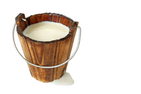 wooden bucket filled with fresh milk isolated