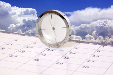 appointments: clock on calendar against a cloudy sky