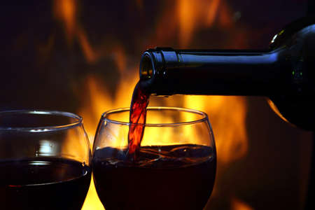 cosy: pouring wine by the fireplace