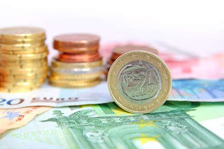 downgrade: greek euro coin on bills