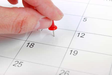 het plaatsen van een punaise op de kalender Stockfoto