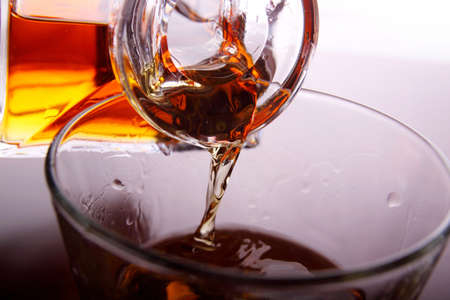 whiskey being poured into a glass photo