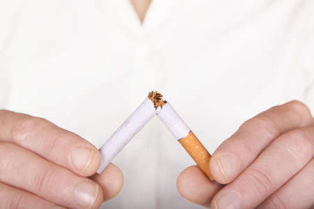 quit smoking: woman breaking a cigarette Stock Photo