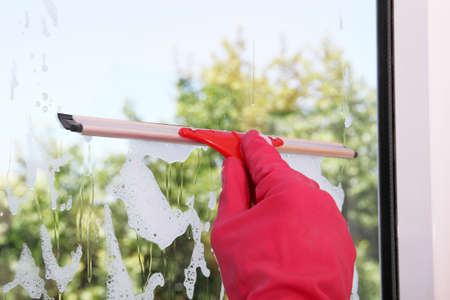 squeegee: hand with squeegee on window pane
