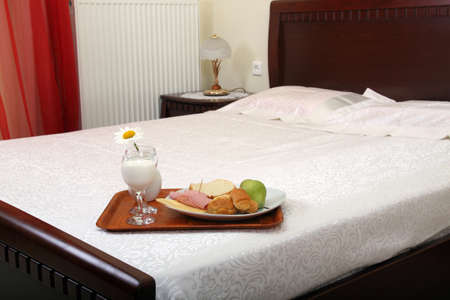tray with breakfast on bed photo