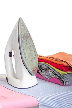 iron on ironing board with clothes photo