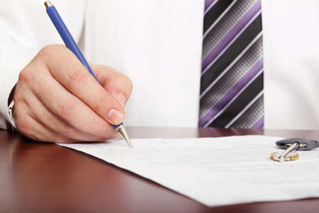 document with key on it is being signed Stock Photo - 14501181