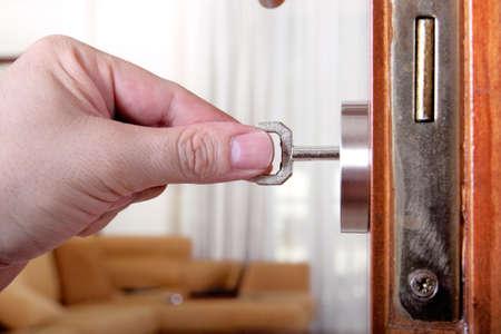 locking: man is locking or unlocking a door