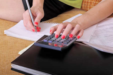 home expenses: woman on sofa is calculating Stock Photo