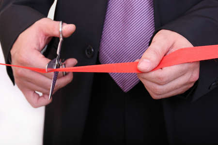businessman cutting red ribbon closeup photo
