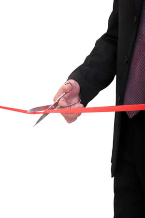 ribbon cutting: businessman is cutting red ribbon