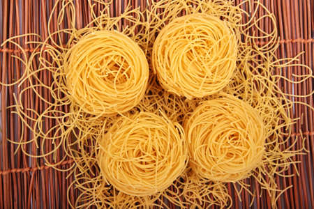 chinese noodle: four egg noodles on bamboo background Stock Photo