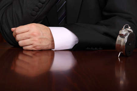 formally dressed man at a desk with a clock on it Stock Photo - 16255437