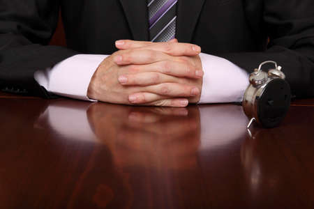 clock in front of formally dressed man at a desk office Stock Photo - 16255447