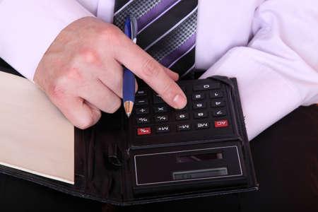 formally dressed man using the calculator closeup photo