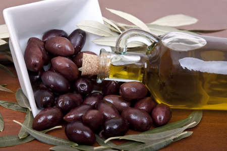 olive oil in carafe and olives closeup photo