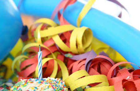 blow out:  birthday candle among balloons and streamers Stock Photo