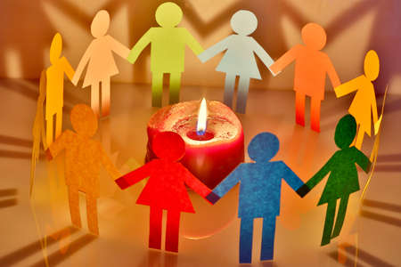 hope concept: paper people around a burning candle