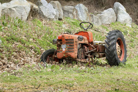 abandoned old orange tractor in the countryside photo