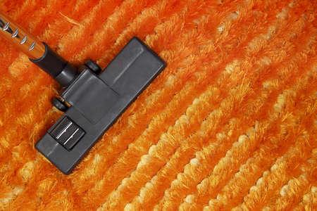 dirty carpet: vacuum cleaner on orange carpet