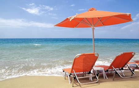 sunbeds: orange sunbeds and umbrella on beach