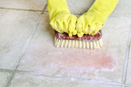 scrubbing: hands in rubber gloves scrubbing the floor Stock Photo