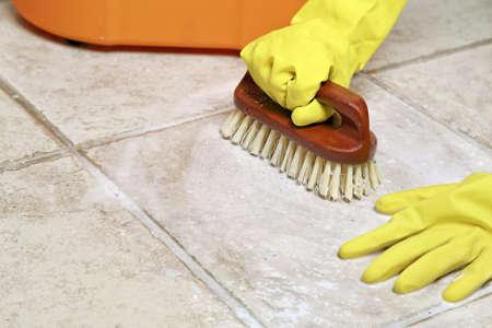 servicio domestico: manos en guantes de goma fregar el suelo Foto de archivo