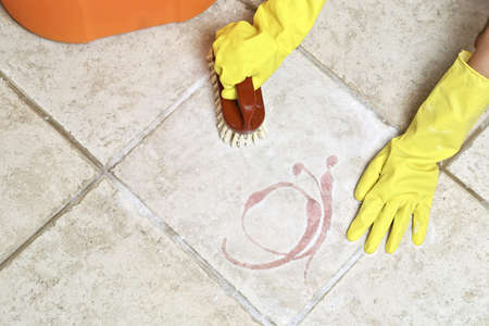 water sanitation: hands in rubber gloves scrubbing the floor Stock Photo