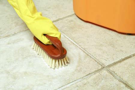 wet floor: hand in rubber glove scrubbing the floor