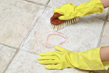 scrubbing: hands in rubber gloves scrubbing the tiles Stock Photo