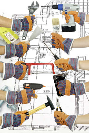 hands holding various tools on blueprint photo