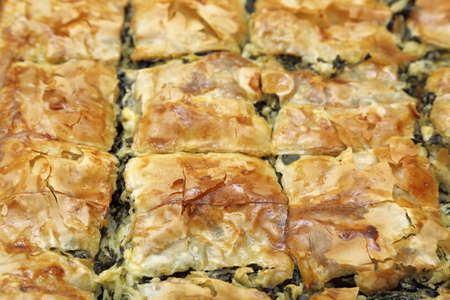 filo pastry: homemade spinach pie cut in square pieces closeup